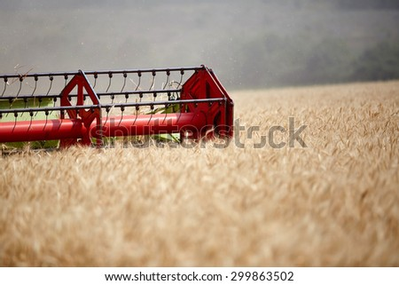 An agricultural combine cutting and harvesting wheat in the fertile farm fields  - stock photo