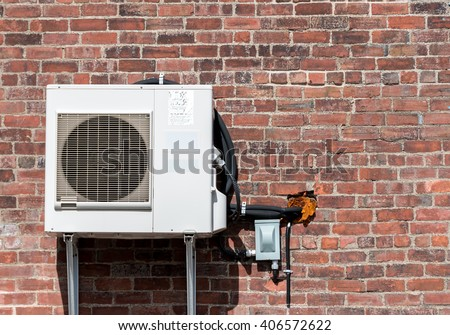 An air conditioning unit on an old brick wall. Cable and hoses run into the wall through a hole with insulation. There is room for text.