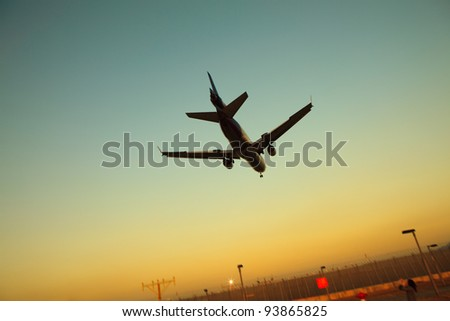 An air jet is landing with the sunset - stock photo