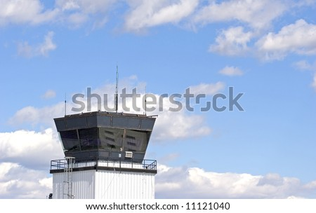 An air traffic control tower at a small regional airport against a blue sky with white puffy clouds - stock photo