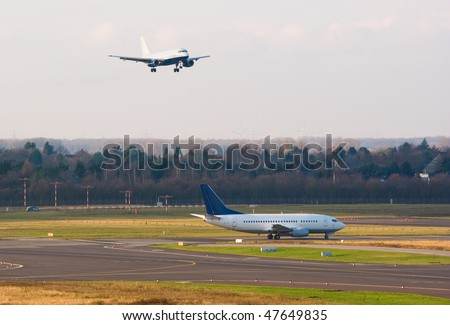 An airplane approaches to land while another one prepare for taking off
