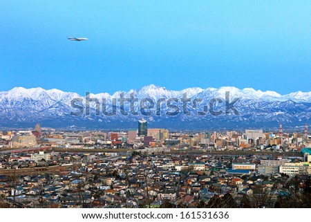 An airplane flying above a large city surrounded by mountains. - stock photo