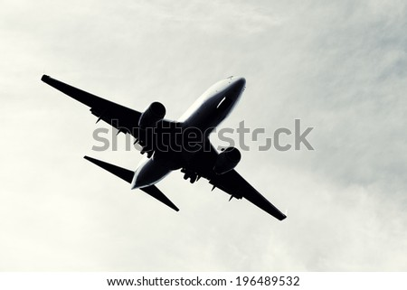 An airplane flying in a white, cloudy sky. - stock photo