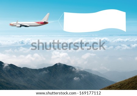 An airplane flying through the sky pulling a blank white banner to add your own message. - stock photo