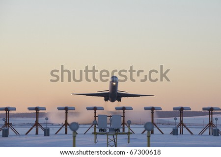 An airplane taking off on a cold winters morning - stock photo