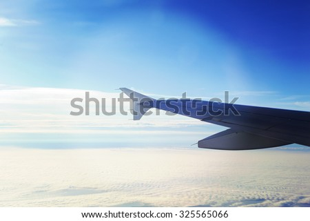 An airplane wing against the sky and clouds up in the air. Image has a strong vintage effect applied. - stock photo