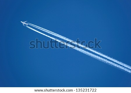 An Airplane with contrail high in the sky - stock photo