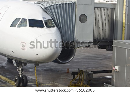 An airplane, with the gangway attached is ready for boarding. - stock photo