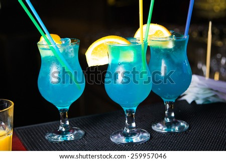 an alcoholic blue cocktail is in beautiful glass, on the bar - stock photo