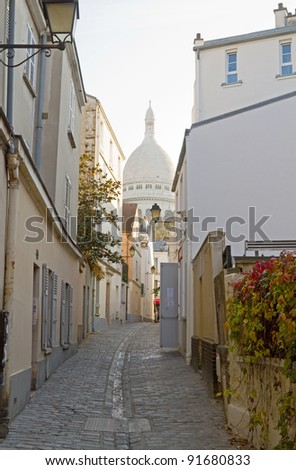 An alley in the picturesque area of Montmartre, Paris, with the church of Sacre-Coeur at the background - stock photo