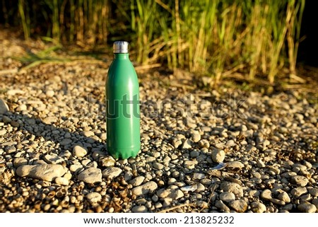 an Aluminium thermos Water Bottle in the nature background - stock photo