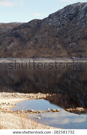 An amazing scenic view of a lake infront of a mountain in the north of Scotland on a sunny day
