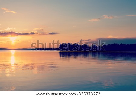 An amazing sunset by the lake. Image taken in Finland during late evening. Image has a vintage effect applied. - stock photo