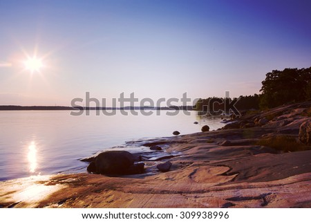 An amazing sunset by the sea. Image taken in Finland during summer evening. Image has a vintage effect applied and some windmills are in the background. - stock photo