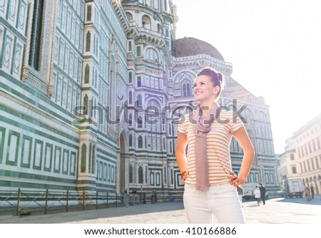 An amble around awe-inspiring Duomo in Florence, Italy. Smiling young woman tourist standing in the front of Duomo and looking into the distance - stock photo