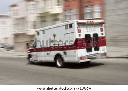An ambulance blazes by, it's sirens whaling.  An intensional camera blur gives a feeling of a rushed tension to the scene. - stock photo
