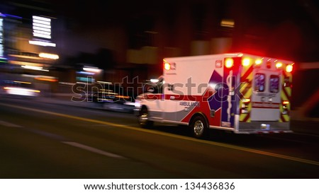 An ambulance speeding through traffic at nighttime - stock photo