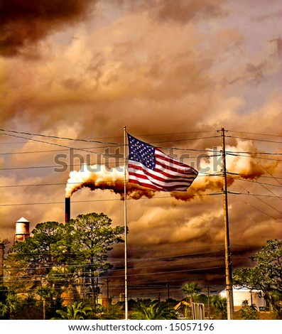 An American flag blowing in the wind in front of an industrial plant - stock photo