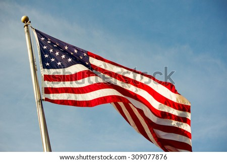 An American flag blowing in the wind on a blue cloudscape/Fluttering American Flag/A USA flag blowing in the wind