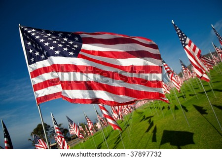An American flag flies in the wind against a background of hundreds of other flags