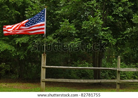 An American flag flying high and proud on a fence along the woods with room for your text. - stock photo