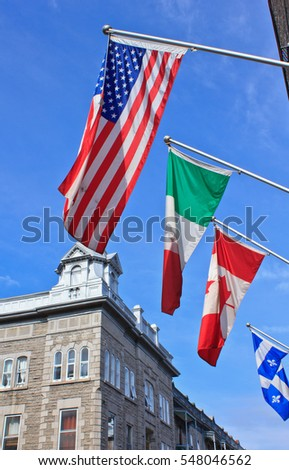 An American flag, Italian flag, Canadian flag, and Quebec flag set against the blue sky in the historic old town of Quebec City, Canada.