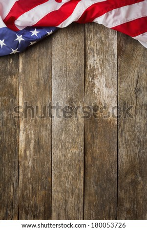 An American Flag Lying on an aged, weathered rustic wooden Background. - stock photo
