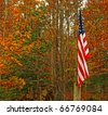 An American flag of the USA on a post during a fall day using selective focus with room for your text. - stock photo