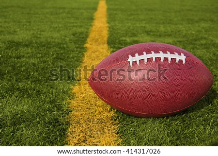 An American football resting just over the goal line for a touchdown. - stock photo