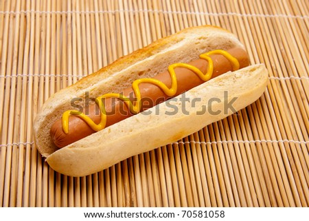 An American hot dog with mustard. - stock photo
