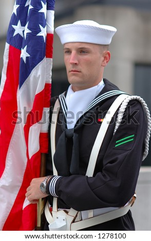 An American navy holding US.  flag - stock photo