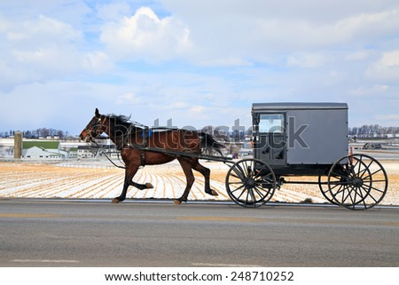 An Amish Carriage travels in snow covered rural Lancaster County, Pennsylvania, USA. - stock photo