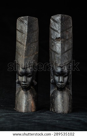 an ancient african black wood carved artifact isolated over a black background - stock photo