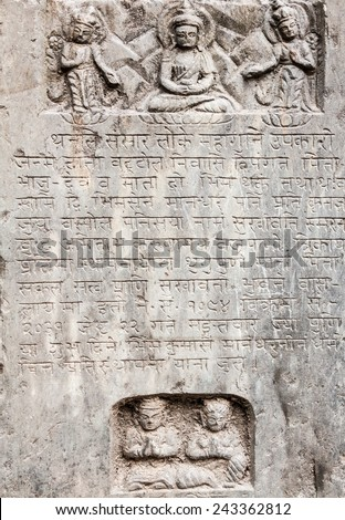 An ancient Buddhist text in Sanskrit etched into a stone tablet. - stock photo