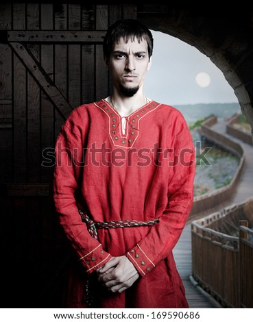 an ancient Bulgarian peasant in front of castle gate - stock photo