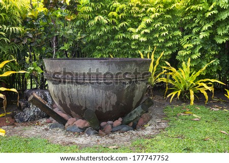 An ancient cast iron cauldron rests on a fire pit ready to burn.  - stock photo