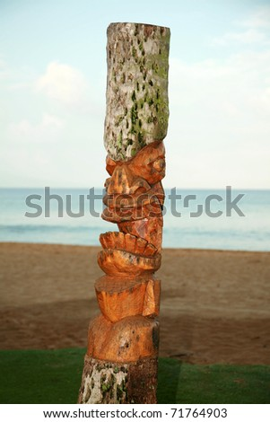 an ancient deity of Hawaiian residents carved out of an old palm tree trunk also known as a Tiki God - stock photo