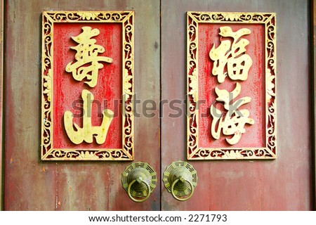 "An ancient door with the sculptured chinese characters, which mean ""Sea of Happiness and Mountain of Life."" - stock photo"