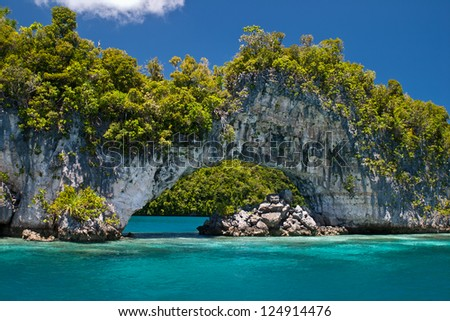An ancient reef, uplifted millions of years ago, now serves as a limestone island set in the midst of Palau's scenic Rock Islands. - stock photo