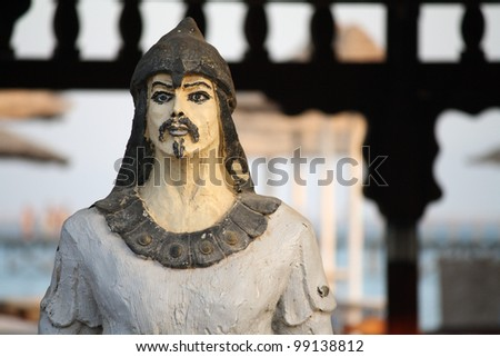 An ancient warrior statue in front of a gate - stock photo