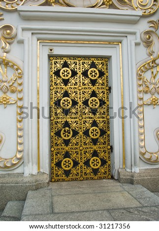 An ancient wooden door with wrought iron ornaments - stock photo