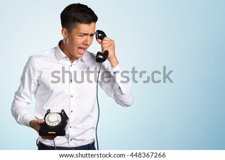 An angry and irritated young man screams into the telephone receiver