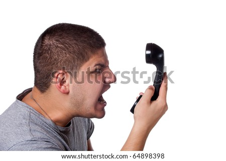 An angry and irritated young man screams into the telephone receiver over a white background.