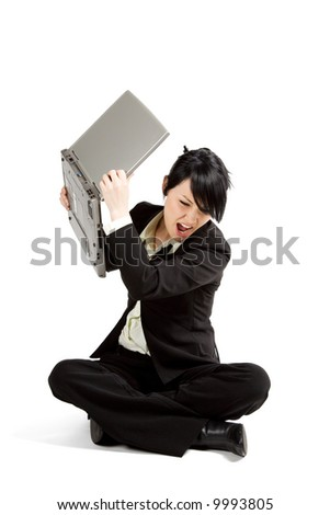 An angry and stressed businesswoman throwing away her laptop - stock photo