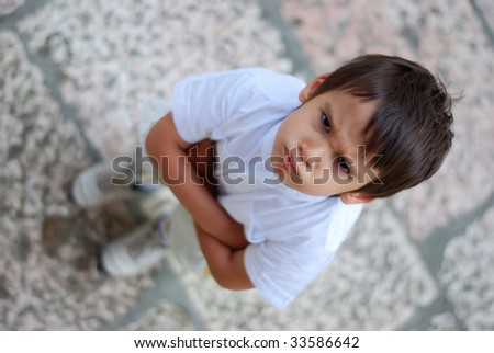 An angry boy with acrossed hands on chest - stock photo