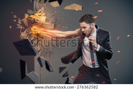 An angry businessman hitting concrete wall - stock photo