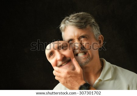 An angry, emotional, depressed, bipolar disorder man is revealing his true self as he takes off a fake smile happiness mask that looks exactly like his face.  - stock photo