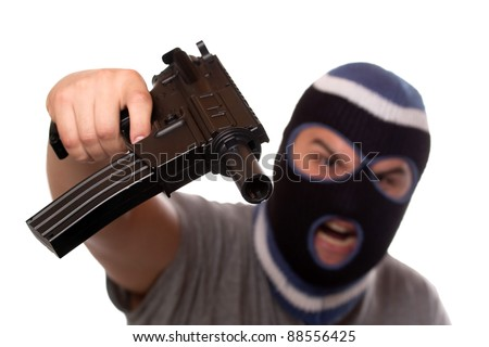 An angry looking man wearing a ski mask pointis a black automatic machine gun at the viewer. Shallow depth of field with sharpest focus on the gun. - stock photo
