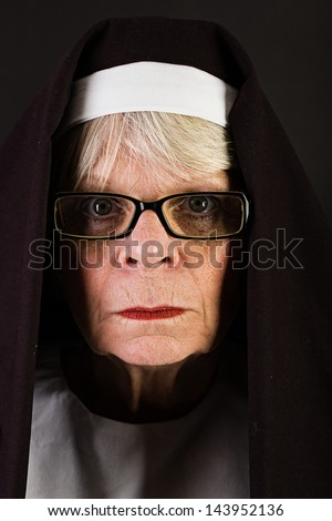 An angry looking mature nun with an intense expression. - stock photo