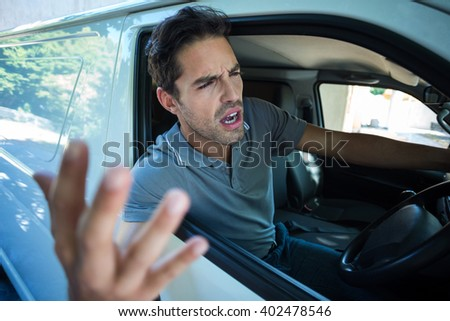 An Angry man is gesturing with his hand while sitting in car